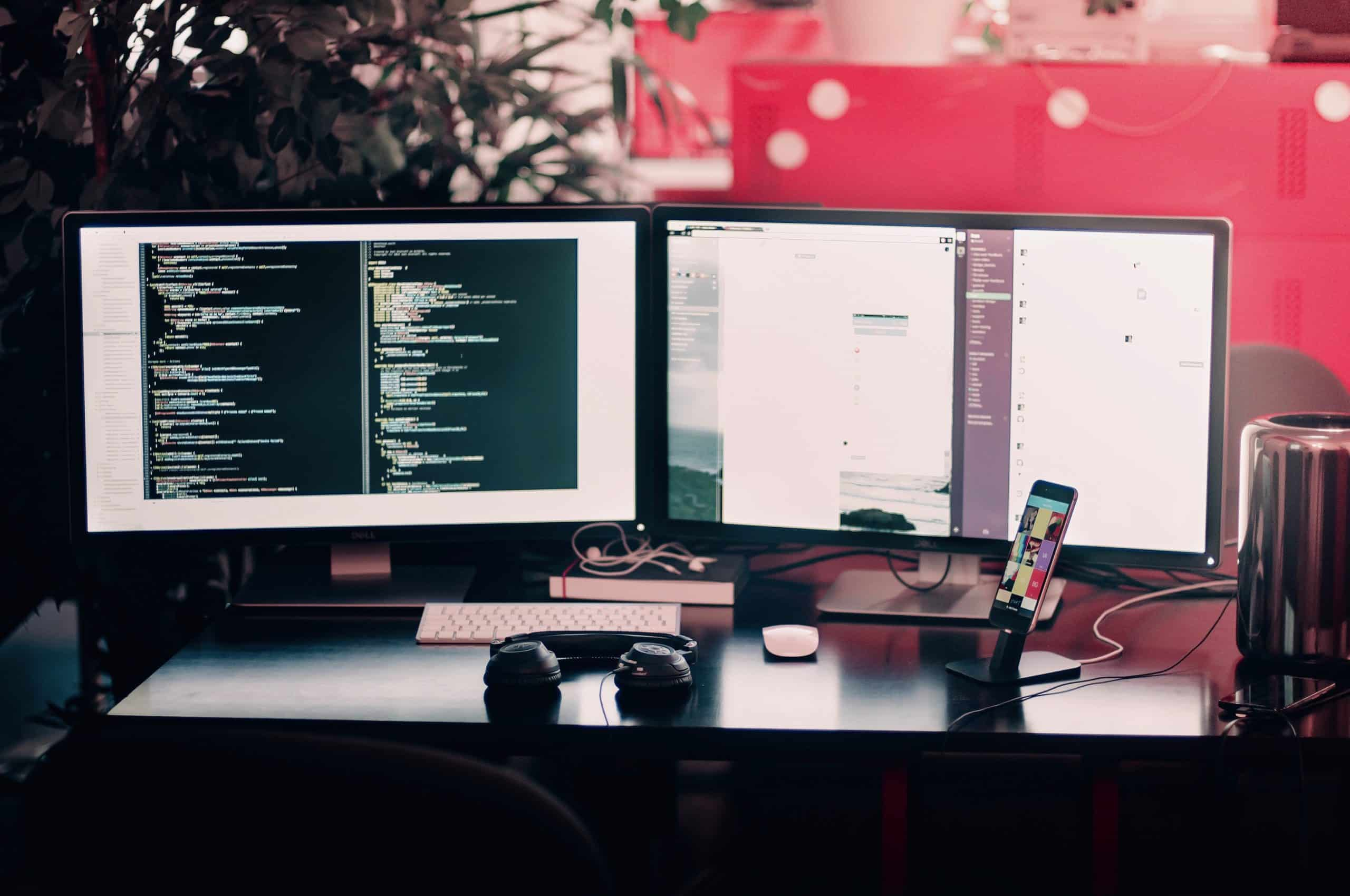 A web developers workstation with dual screens, mobile phone and headphones on the desk